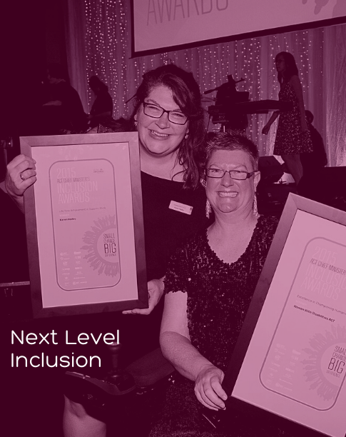 Two people holding up certificates in frames. Both people have huge grins on their faces. One is standing and one is sitting in a wheelchair.